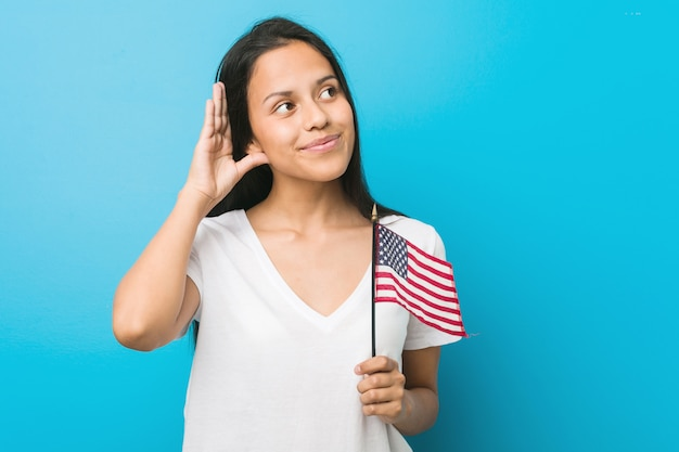Jovem mulher hispânica, segurando uma bandeira dos estados unidos, tentando ouvir uma fofoca.