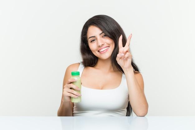 Jovem mulher hispânica, segurando uma bebida vegetal, mostrando o número dois com os dedos