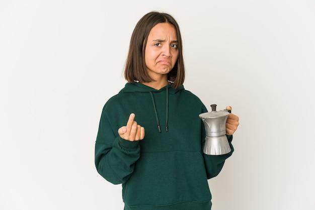 Jovem mulher hispânica segurando uma cafeteira apontando com o dedo para você como se fosse um convite para se aproximar.