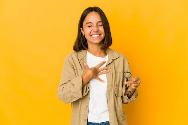 Jovem mulher hispânica segurando uma chave velha ri alto, mantendo a mão no peito.