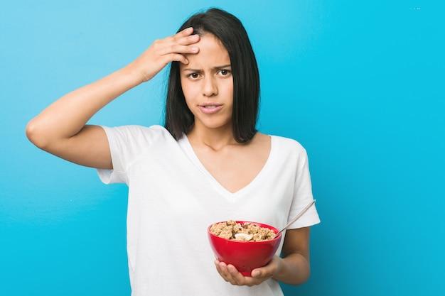 Jovem mulher hispânica segurando uma tigela de cereal sendo chocada, lembrou-se de uma reunião importante.