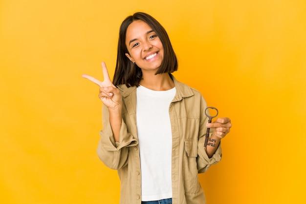 Jovem mulher hispânica segurando uma velha chave alegre e despreocupada, mostrando um símbolo de paz com os dedos.