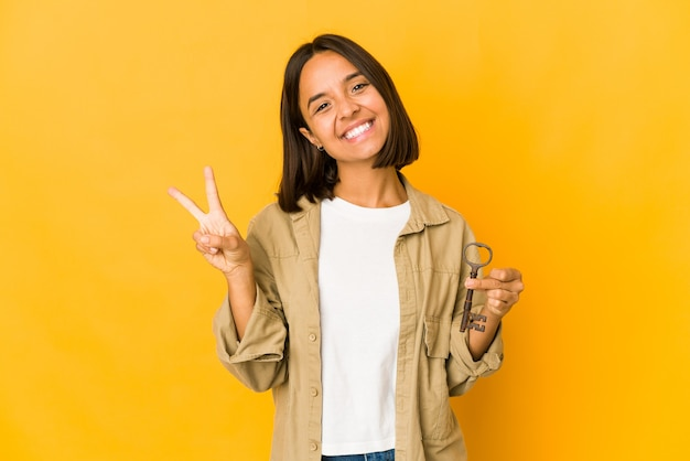 Jovem mulher hispânica segurando uma velha chave mostrando o número dois com os dedos.