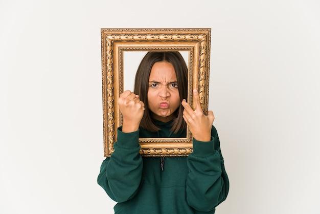 Jovem mulher hispânica segurando uma velha moldura mostrando o punho, expressão facial agressiva.