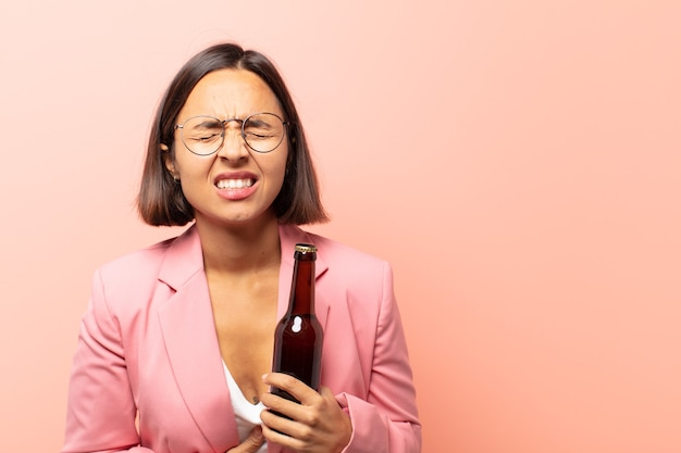 Jovem mulher hispânica sentindo-se ansiosa, doente, doente e infeliz, com dor de estômago ou gripe