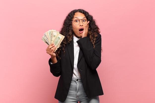 Jovem mulher hispânica, sentindo-se chocada e com medo, parecendo apavorada com a boca aberta e as mãos nas bochechas. conceito de notas de dólar
