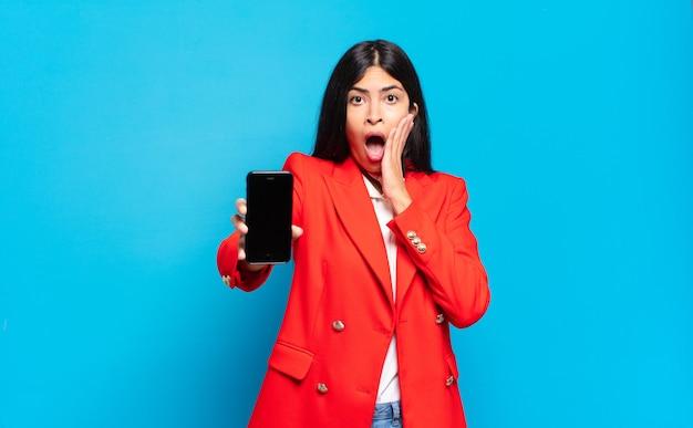 Jovem mulher hispânica, sentindo-se chocada e com medo, parecendo apavorada com a boca aberta e as mãos nas bochechas. espaço de cópia da tela do telefone