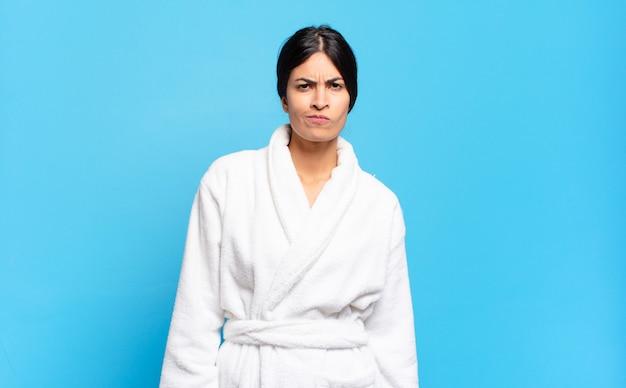 Jovem mulher hispânica sentindo-se confusa e em dúvida, pensando ou tentando escolher ou tomar uma decisão. conceito de roupão de banho