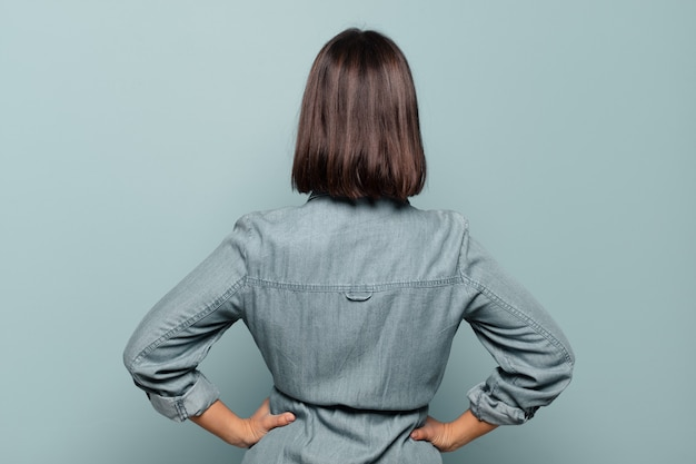 Jovem mulher hispânica sentindo-se confusa ou cheia ou dúvidas e perguntas, imaginando, com as mãos nos quadris, vista traseira