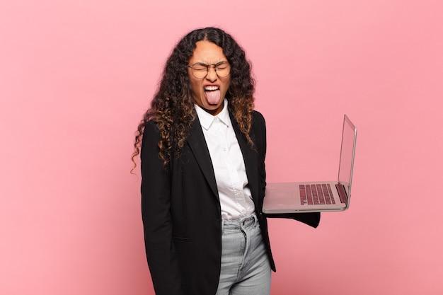 Jovem mulher hispânica sentindo-se enojada e irritada, mostrando a língua, não gostando de algo nojento e nojento