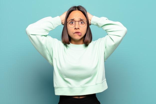 Jovem mulher hispânica sentindo-se estressada, preocupada, ansiosa ou assustada, com as mãos na cabeça, entrando em pânico com o erro