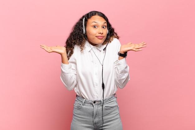 Jovem mulher hispânica sentindo-se perplexa e confusa, duvidando, ponderando ou escolhendo diferentes opções com expressão engraçada. conceito de telemarketing