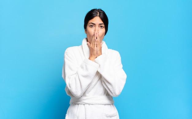 Jovem mulher hispânica sentindo-se preocupada, chateada e assustada, cobrindo a boca com as mãos, parecendo ansiosa e tendo bagunçado tudo. conceito de roupão de banho