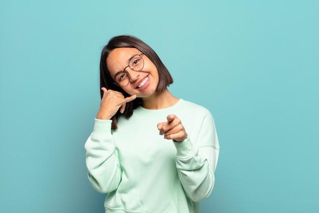 Jovem mulher hispânica sorrindo alegremente e apontando enquanto faz um gesto para ligar para você, falando ao telefone