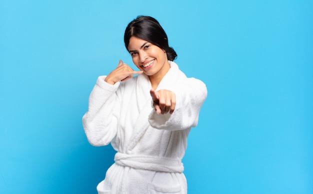 Jovem mulher hispânica sorrindo alegremente e apontando para a câmera ao fazer um gesto de chamá-lo mais tarde, falando no telefone. conceito de roupão de banho