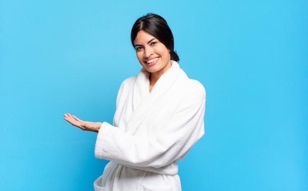 Jovem mulher hispânica sorrindo alegremente, sentindo-se feliz e mostrando um conceito no espaço da cópia com a palma da mão. conceito de roupão de banho