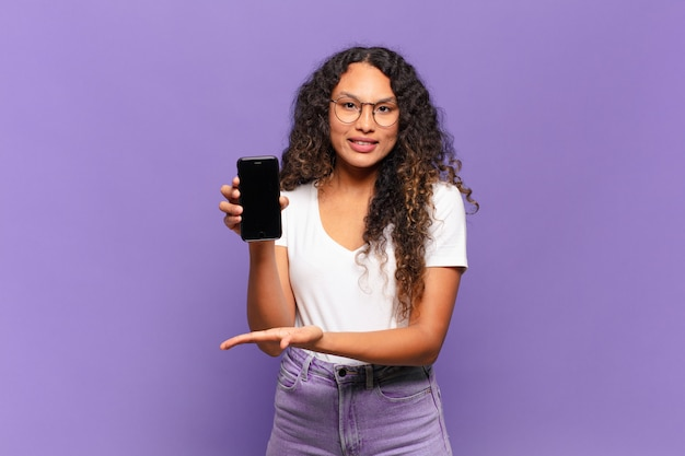 Jovem mulher hispânica sorrindo alegremente, sentindo-se feliz e mostrando um conceito no espaço da cópia com a palma da mão. conceito de telefone inteligente