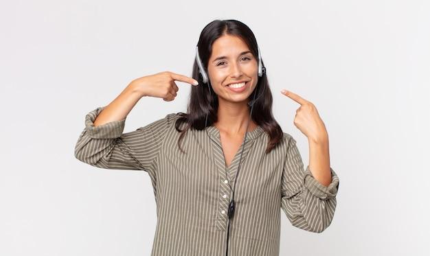 Jovem mulher hispânica sorrindo com confiança, apontando para o próprio sorriso largo com um fone de ouvido. conceito de telemarketing