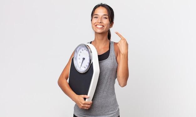 Jovem mulher hispânica sorrindo com confiança, apontando para o próprio sorriso largo e segurando uma balança. conceito de dieta