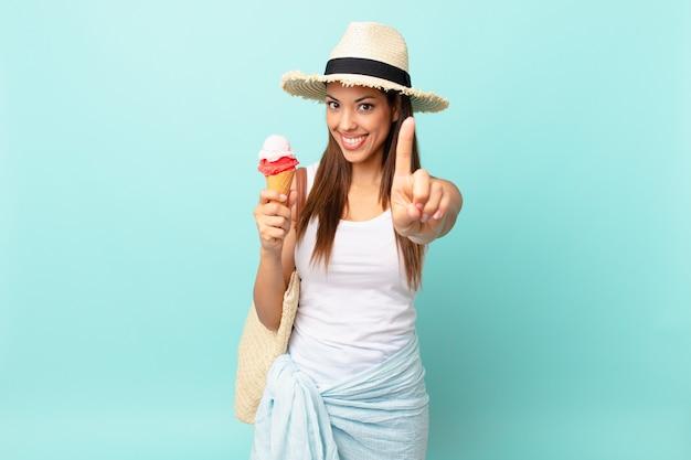 Jovem mulher hispânica sorrindo com orgulho e confiança, fazendo o número um e segurando um sorvete. conceito de sumer
