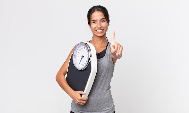 Jovem mulher hispânica sorrindo com orgulho e confiança, fazendo o número um e segurando uma balança. conceito de dieta