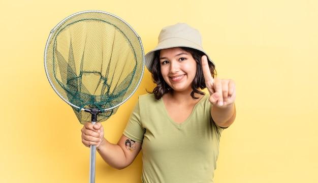 Jovem mulher hispânica sorrindo com orgulho e fazendo o número um com confiança. conceito de rede de pesca