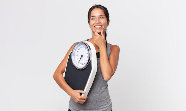 Jovem mulher hispânica, sorrindo com uma expressão feliz e confiante, com a mão no queixo e segurando uma balança. conceito de dieta