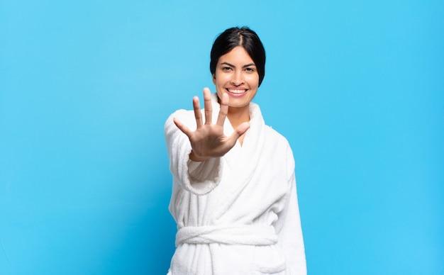 Jovem mulher hispânica sorrindo e parecendo amigável, mostrando o número cinco ou quinto com a mão para a frente, em contagem regressiva. conceito de roupão de banho