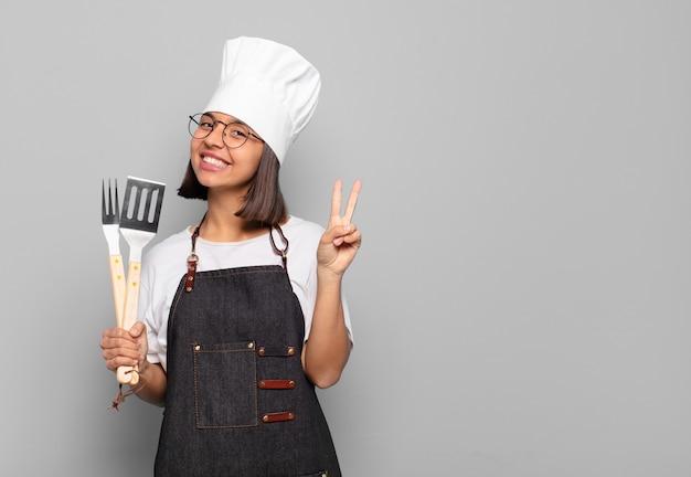 Jovem mulher hispânica sorrindo e parecendo amigável, mostrando o número dois ou o segundo com a mão para a frente, em contagem regressiva