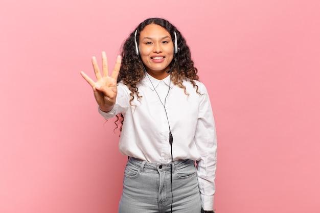 Jovem mulher hispânica sorrindo e parecendo amigável, mostrando o número quatro ou quarto com a mão para a frente, em contagem regressiva. conceito de telemarketing