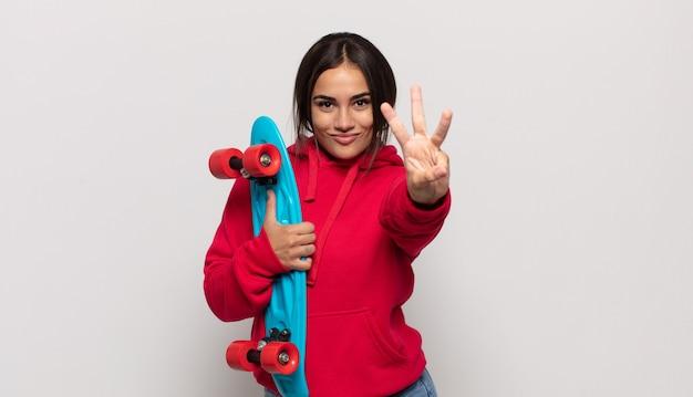 Jovem mulher hispânica sorrindo e parecendo amigável, mostrando o número três ou o terceiro com a mão para a frente, em contagem regressiva