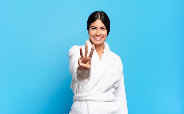 Jovem mulher hispânica sorrindo e parecendo amigável, mostrando o número três ou terceiro com a mão para a frente, em contagem regressiva. conceito de roupão de banho