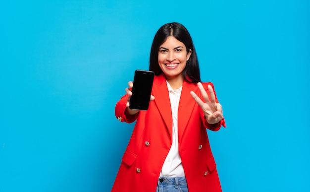 Jovem mulher hispânica sorrindo e parecendo amigável, mostrando o número três ou terceiro com a mão para a frente, em contagem regressiva. espaço de cópia da tela do telefone