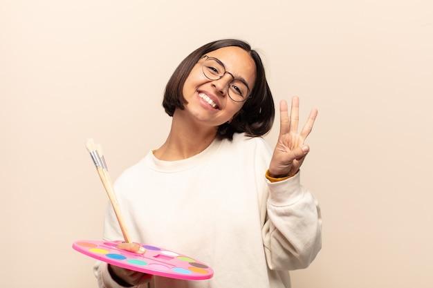 Jovem mulher hispânica sorrindo e parecendo amigável, mostrando o número três ou terceiro com a mão para a frente, em contagem regressiva