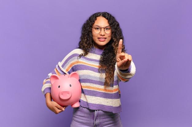 Jovem mulher hispânica sorrindo e parecendo amigável, mostrando o número um ou primeiro com a mão para a frente, em contagem regressiva. conceito de cofrinho