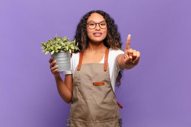 Jovem mulher hispânica sorrindo e parecendo amigável, mostrando o número um ou primeiro com a mão para a frente, em contagem regressiva. conceito de jardineiro