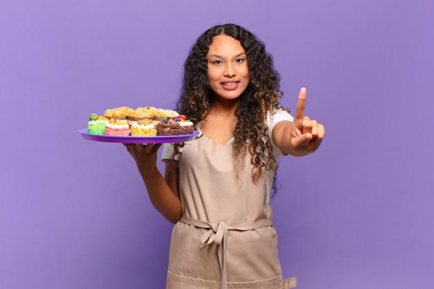 Jovem mulher hispânica sorrindo e parecendo amigável, mostrando o número um ou primeiro com a mão para a frente, em contagem regressiva. cozinhar bolos conceito