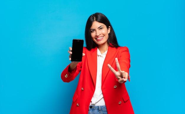 Jovem mulher hispânica sorrindo e parecendo feliz, despreocupada e positiva, gesticulando vitória ou paz com uma mão. espaço de cópia da tela do telefone