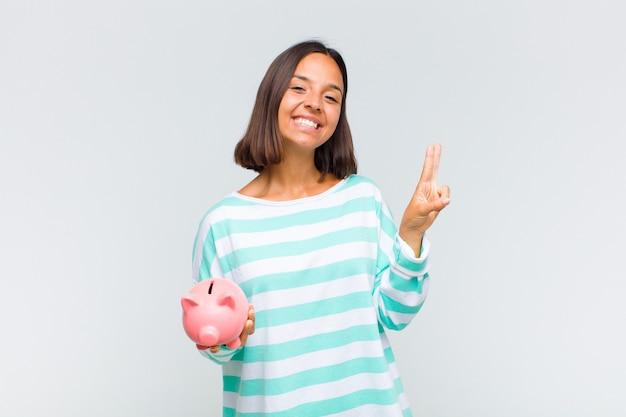 Jovem mulher hispânica sorrindo e parecendo feliz, despreocupada e positiva, gesticulando vitória ou paz com uma mão