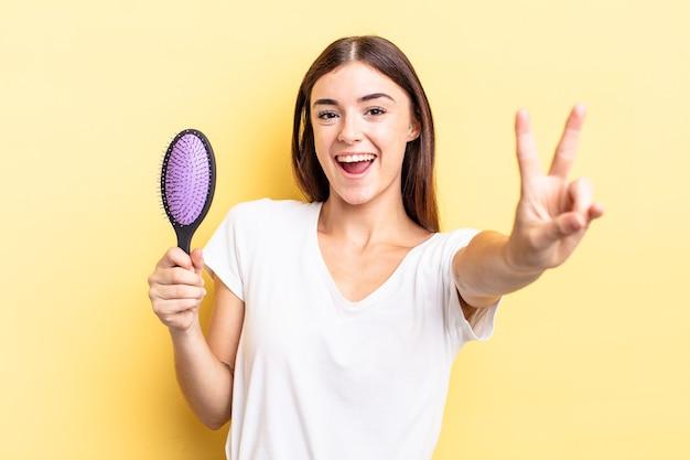 Jovem mulher hispânica sorrindo e parecendo feliz, gesticulando vitória ou paz. conceito de escova de cabelo