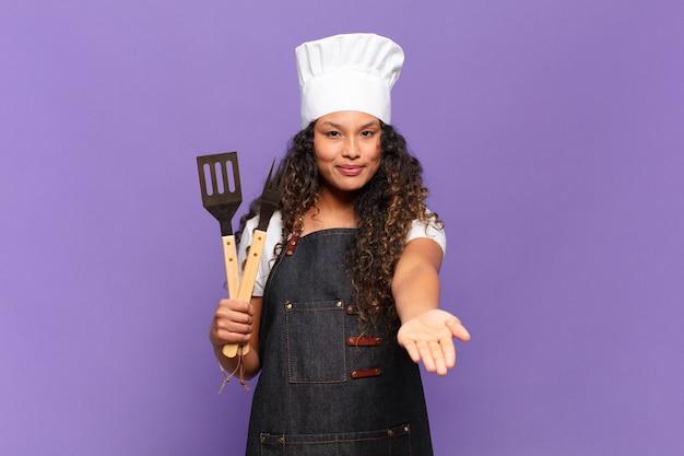 Jovem mulher hispânica sorrindo feliz com olhar amigável, confiante e positivo, oferecendo e mostrando um objeto ou conceito. conceito de chef de churrasco