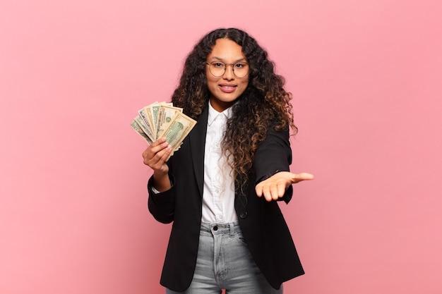 Jovem mulher hispânica sorrindo feliz com olhar amigável, confiante e positivo, oferecendo e mostrando um objeto ou conceito. conceito de notas de dólar