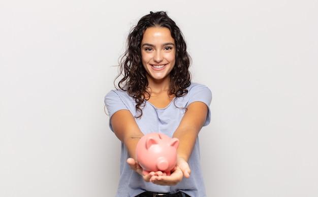 Jovem mulher hispânica sorrindo feliz com um olhar amigável, confiante e positivo, oferecendo e mostrando um objeto ou conceito