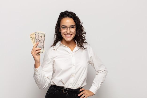 Jovem mulher hispânica sorrindo feliz com uma mão no quadril e uma atitude confiante, positiva, orgulhosa e amigável