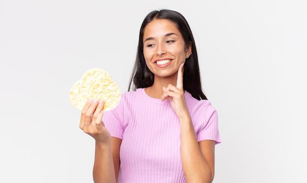 Jovem mulher hispânica sorrindo feliz e sonhando acordada ou duvidando e segurando um biscoito de arroz. conceito de dieta