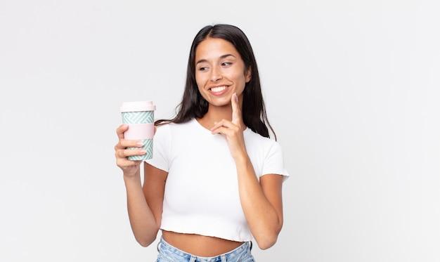 Jovem mulher hispânica sorrindo feliz e sonhando acordada ou duvidando e segurando uma vasilha de café para viagem