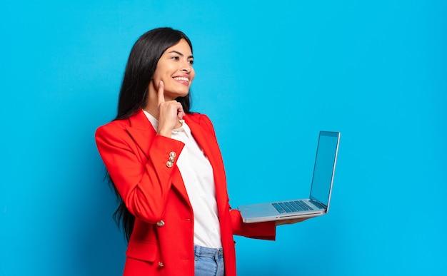 Jovem mulher hispânica sorrindo feliz e sonhando acordada ou duvidando, olhando para o lado. conceito de laptop