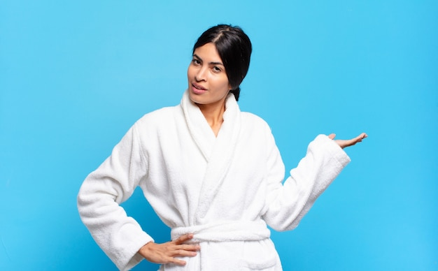 Jovem mulher hispânica sorrindo, sentindo-se confiante, bem-sucedida e feliz, mostrando o conceito ou ideia no espaço da cópia ao lado. conceito de roupão de banho