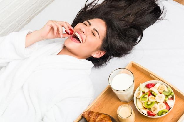 Jovem mulher hispânica, tomando café da manhã na cama