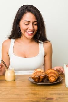 Jovem mulher hispânica, tomando café da manhã na mesa